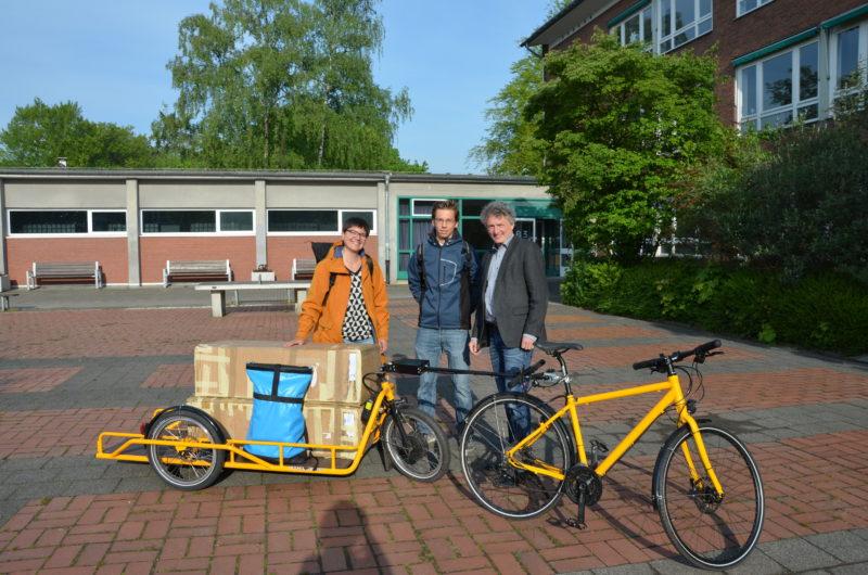 Laura Hebling übergibt für Vamos e.V. die Ausstellung an Schulleiter Christian Schrand und den Schüler Luca Thomas.