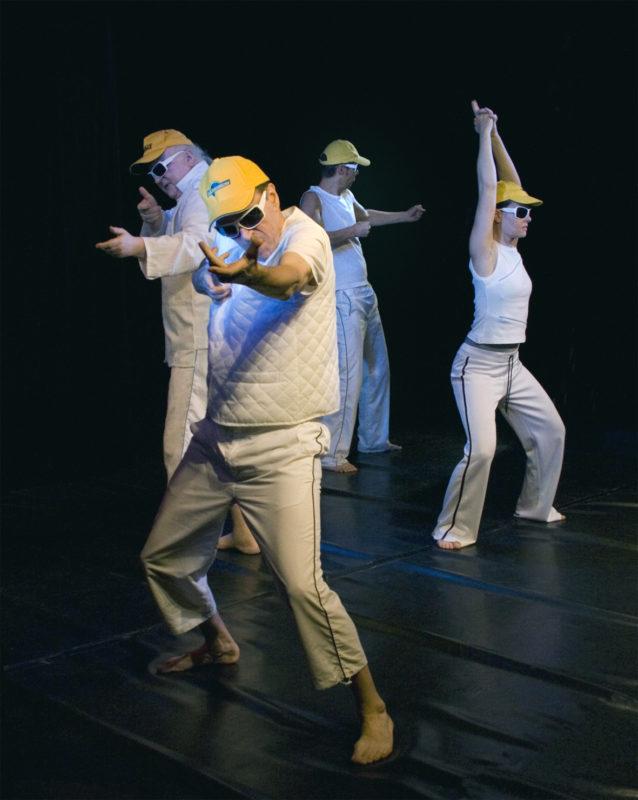 Vier Personen halten unsichtbare Gewehre auf der Bühne