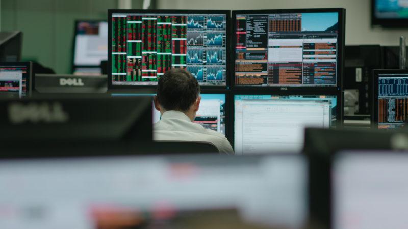 Das Bild zeigt eine Szene aus dem Film mit einem Mitarbeiter, der Aktienentwicklungen analysiert auf mehreren Bildschirmen.