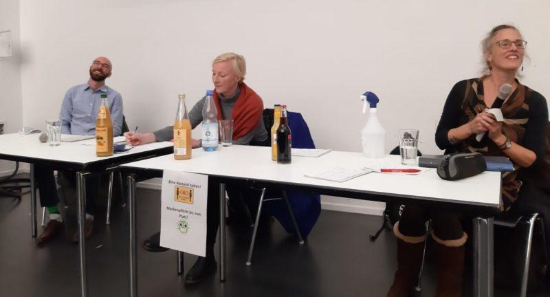 Drei Personen sitzen an einem Tisch, ein der Person hat ein Mikro in der Hand