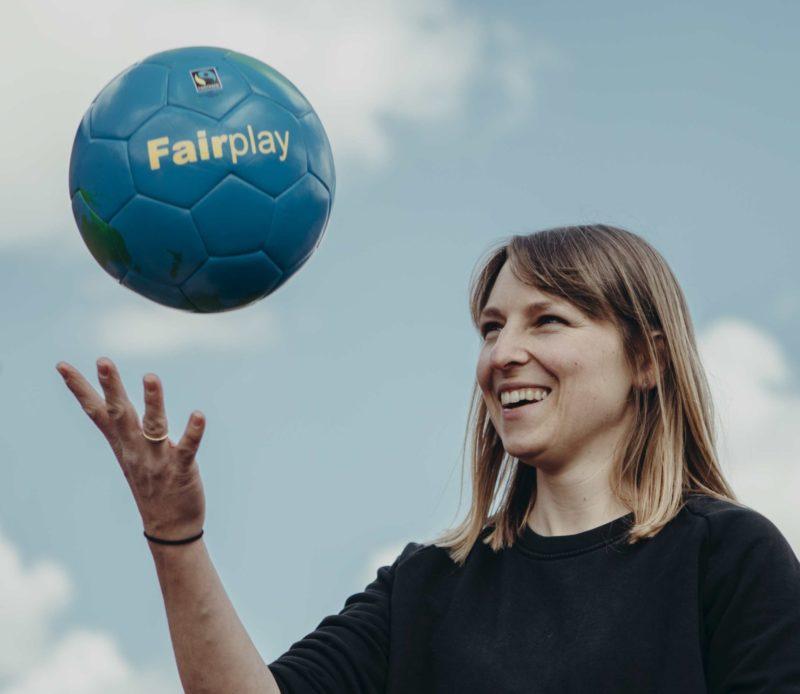 """Frau wirft einen Ball mit dem Schriftzug """"Fairplay"""" in die Luft."""