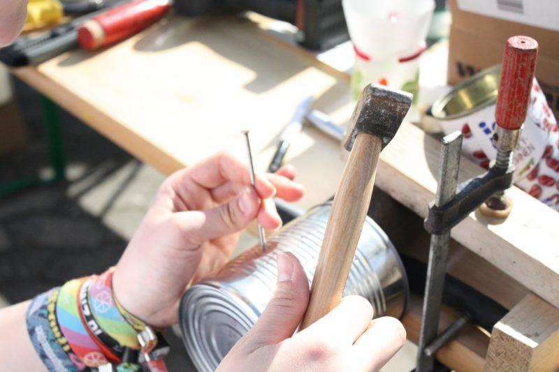 Hände, die eine Blechdose mit Hammer und Nagel upcyclen
