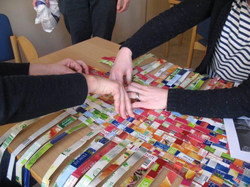 Bild eines Upcyclingproduktes, Korb wird aus Zeitungen von Menschen gefaltet