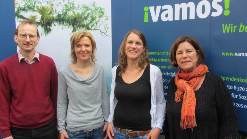 Foto vom Vamos Vorstand, vier Personen vor einem Werbebanner von Vamos