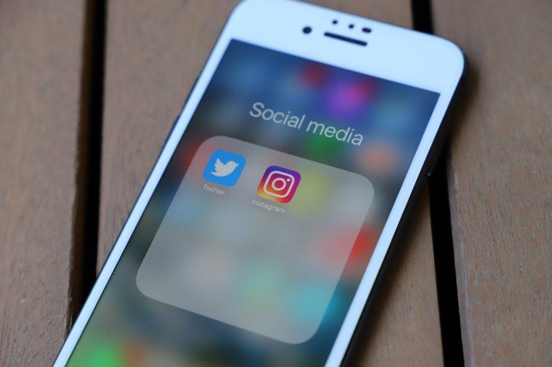 """Smartphone mit einem geöffneten Ordner, in dem sich die Apps """"Twitter"""" und """"Instagram"""" befinden"""