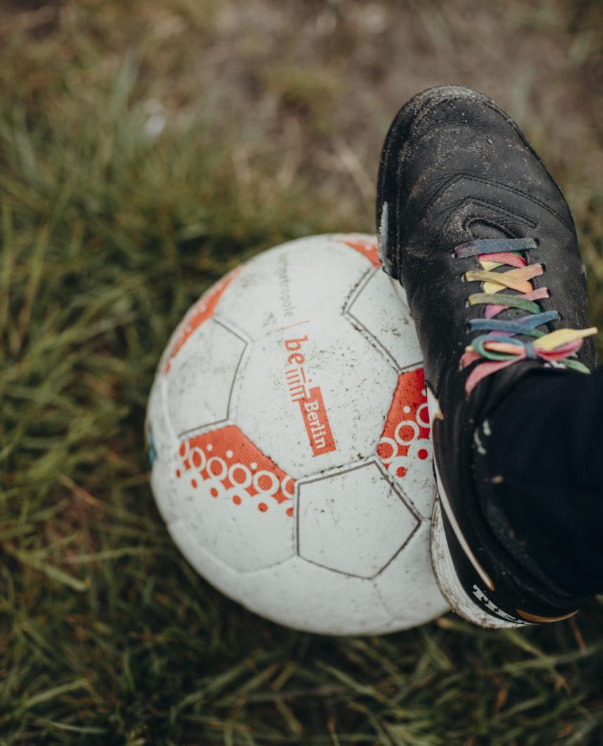 Ein Fuß steht auf einem Fußball
